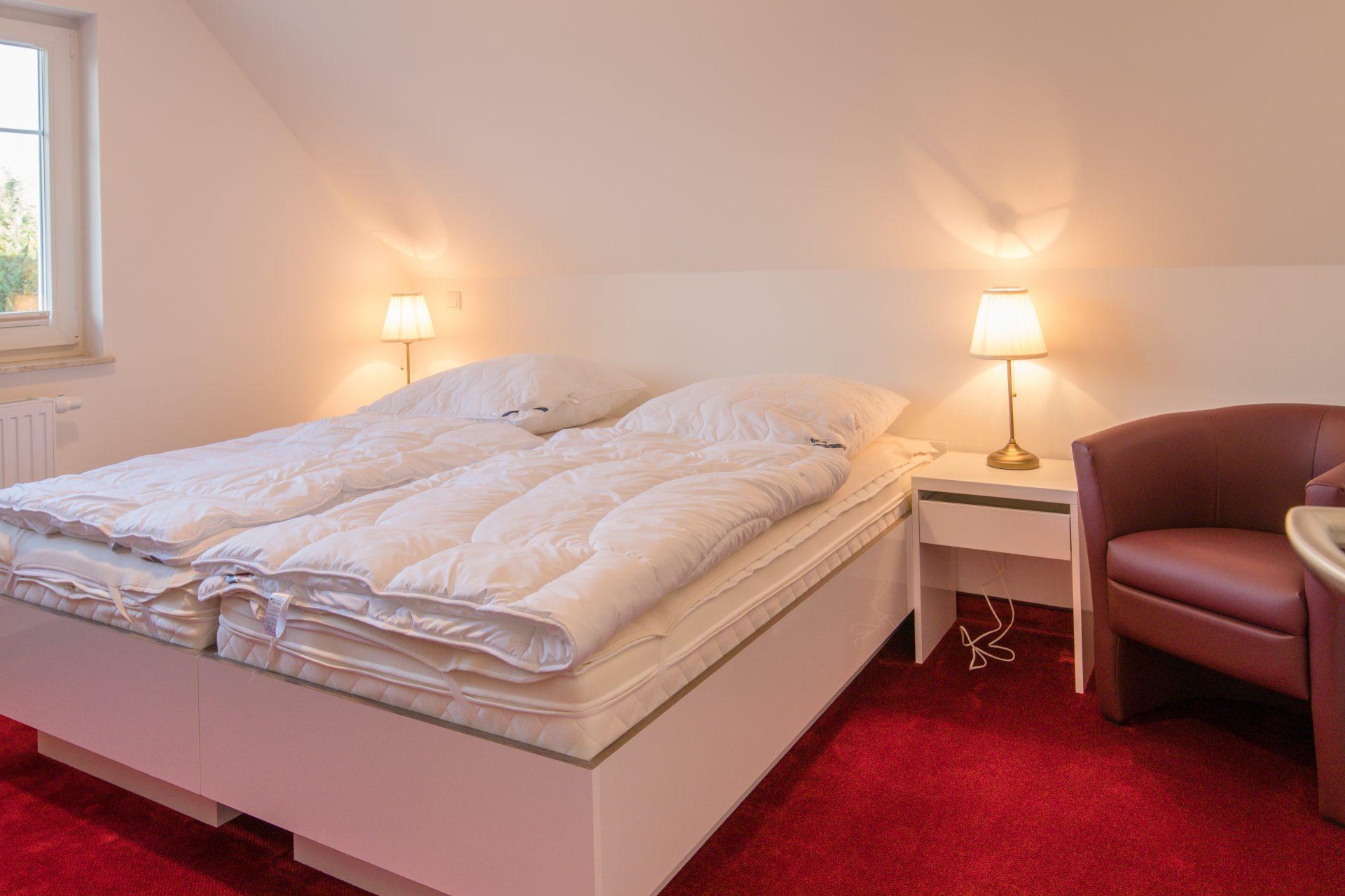 Schlafzimmer mit Doppelbett und Sessel