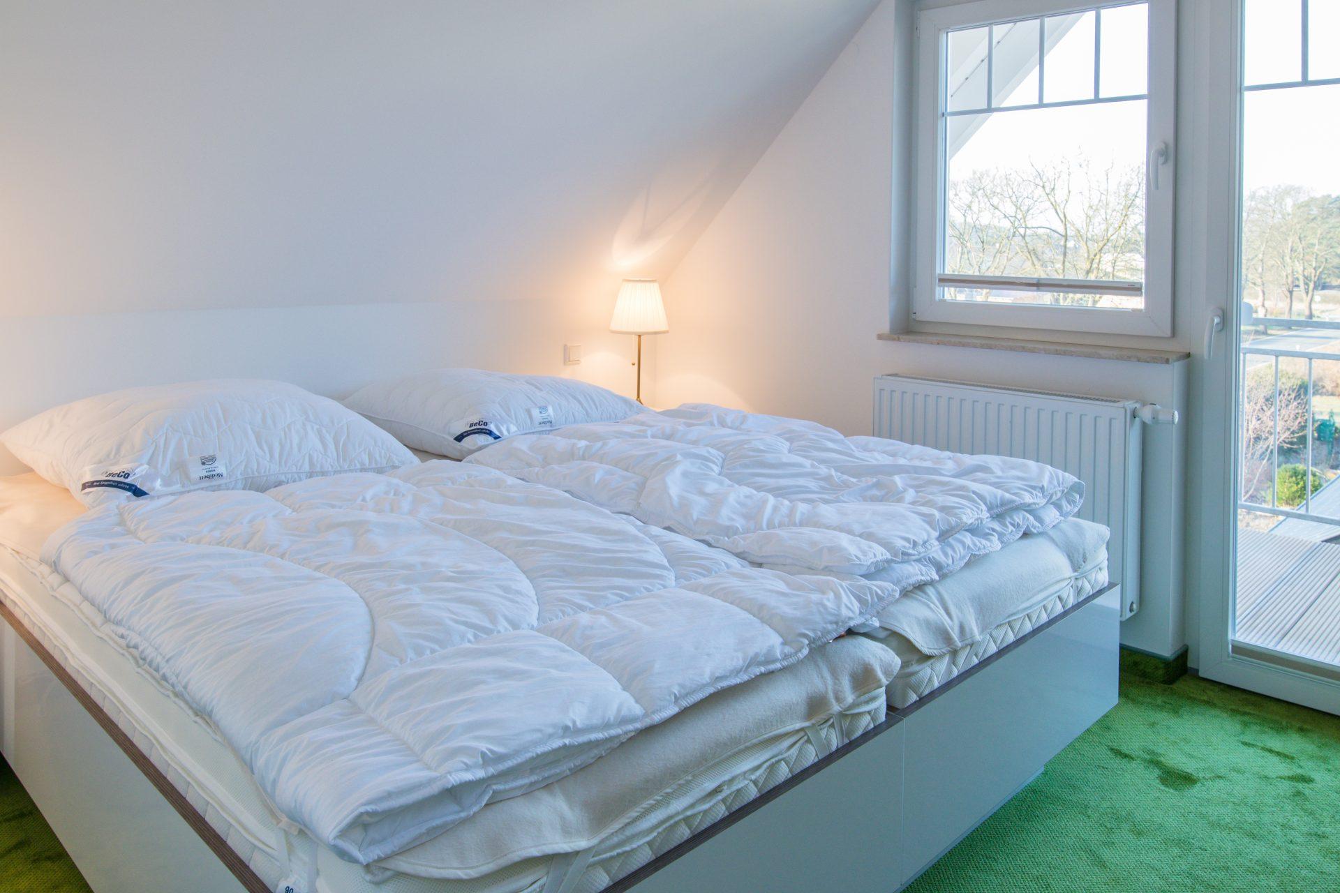 Schlafzimmer mit Doppelbett und eigenem Balkon