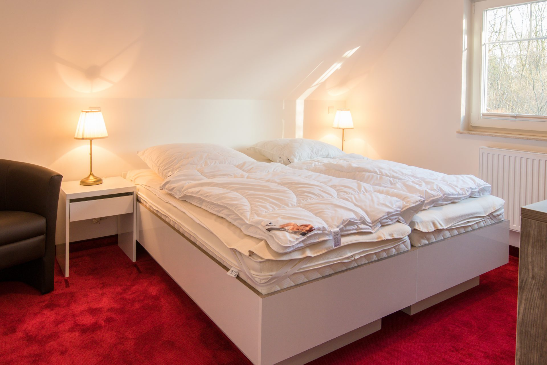Schlafzimmer mit Doppelbett, Sessel und TV