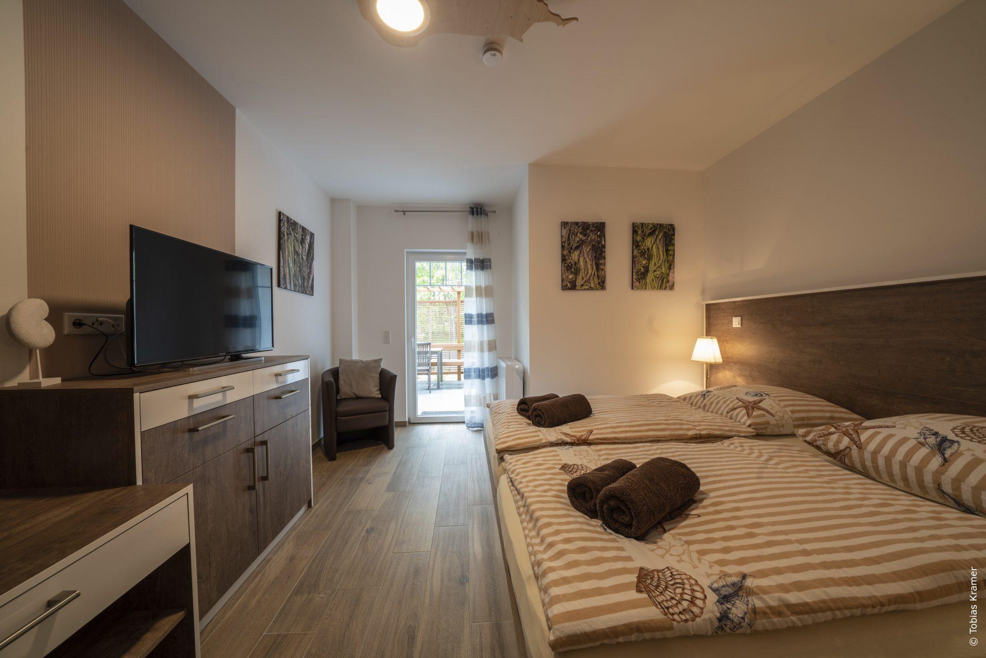 Schlafzimmer mit Doppelbett, Sessel, TV und eigenem Bad